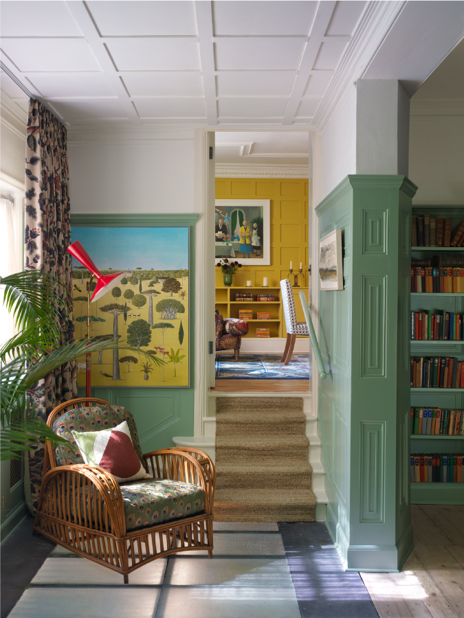 An armchair in a colourful London home by top luxury interior designer studio ashby. The walls are bright yellow and seafoam green with a rattan armchair near a window and a vintage rug.