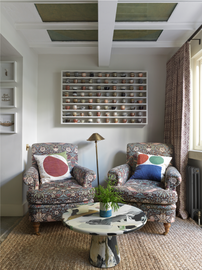 Two armchairs in a cosy corner of a studio ashby designed home in south kensington. there is a terrazzo coffee table and two vintage armchairs with colourful cushion and ceramics on the wall