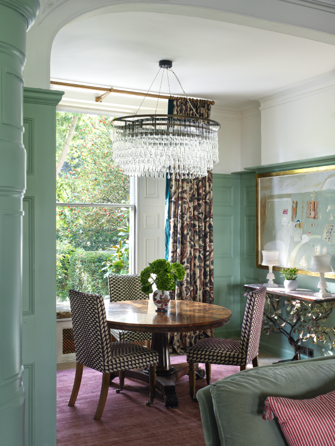 A small cosy vintage wood dining table is perched by a window with three antique dining chairs. There is a vintage chandelier above, the walls are seafoam green and there is a vintage sideboard with a gold-framed photo and a modern lamp.