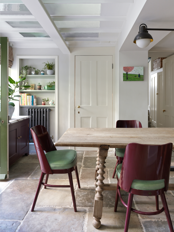 The kitchen/dining area of the studio ashby designed Peter Pan home. The chairs are burgundy and green and the table is a contemporary vintage rectangular wood table. The walls of the kitchen are painted cream and the radiator is painted grey.