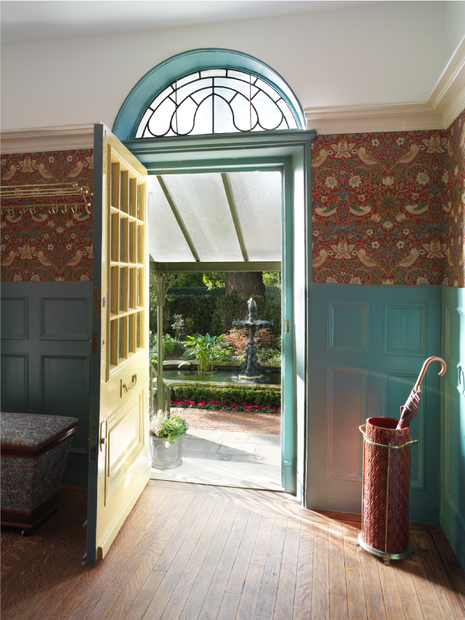 The entryway of an Edwardian six bedroom home designed by luxury interior dsigner studio ashby in south kensignton. The walls are half seafoam green and half red printed wallpaper. The front door is painted yellow.
