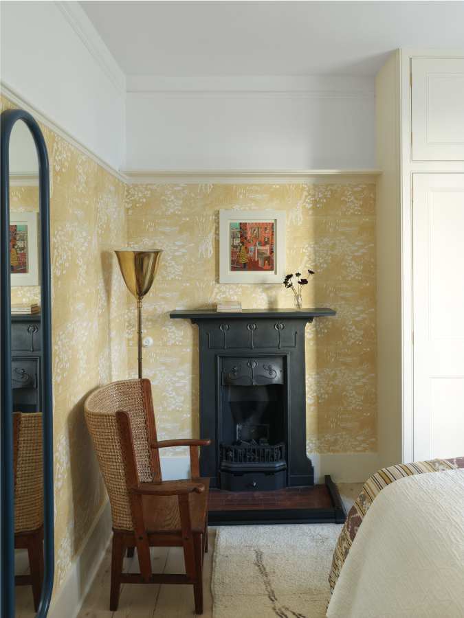 A chic small bedroom with pale yellow wallpaper, a black-rimmed mirror and a fireplace painted matte black. There is a gold lamp in the corner and a rattan armchair.