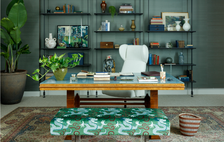 Iconic studio ashby interior designed home office. There is a vintage glass and wood desk with a vintage italian office chair and a built in library with green walls all around.