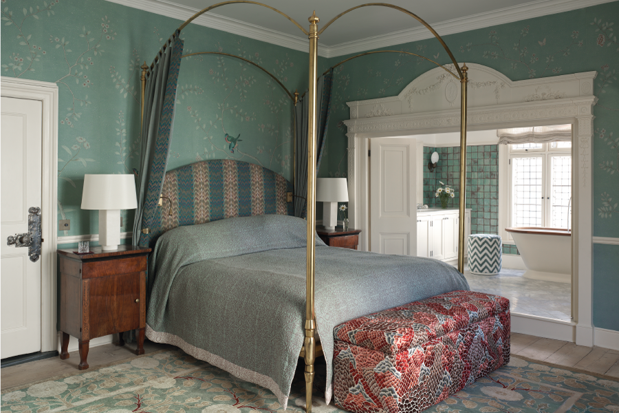 Bedroom with bold seafoam green wallpaper and a four-post bed in brass metal. There is an ensuite bathroom and the antique wood bedside tables have modern bedside table lamps sitting on top. There is a light coloured blue and beige vintage rug and a bench at the foot of the bed.
