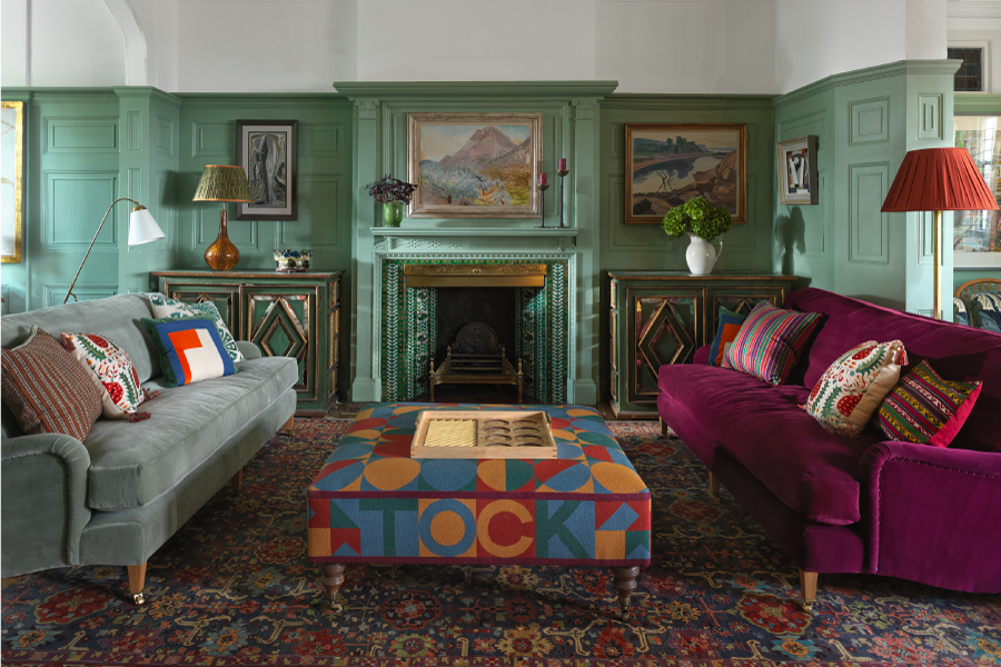 A living room with two velvet sofas, one of the velvet sofas is cherry red and the other is seafoam grey. The sofas have colourful cushions on them and a patchwork colourful ottoman in between. The walls of the room are seafoam green and there is a fireplace. It is all brought together by a vintage red rug.