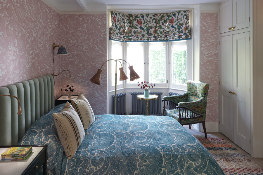 a pink wallpaper covered bedroom with a powder blue bed and antique wardrobe. There is a bay window with a small side table and a vintage armchair.
